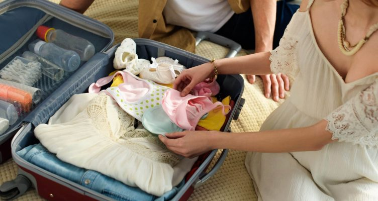 cropped view of pregnant woman and husband packing suitcase for hospital